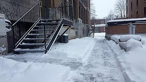 Déneigement manuel d'un accès à un immeuble dans la ville de Québec